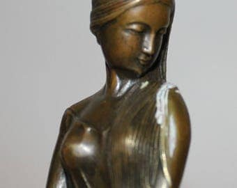 Bronze of shy girl with doll or flowers