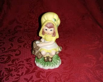 Vintage girl in yellow outfit and bonnet figurine
