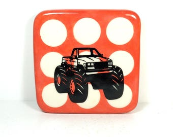 tile in red-orange with a monster truck print. ready to ship