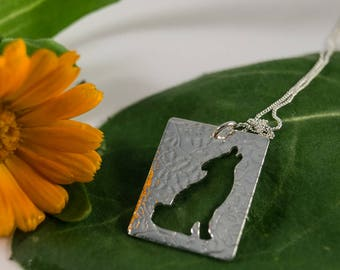 Silver Wolf Pendant: A Howling wolf silhouetted in sterling silver