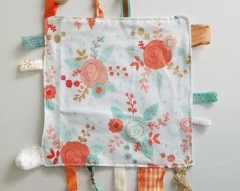 """Teething Chew Tag Blanket for baby. Cotton, ribbon, wood ring pendant, peach & turquoise flowers. 10"""" x 10"""" handmade by Everyday Gourmet"""