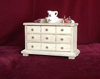 Dollhouse miniature dresser with water basin, towel, and bottle accessories.