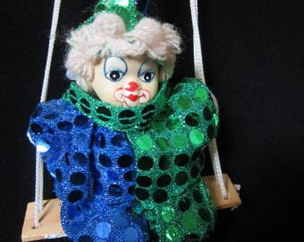Clown On A Swing Christmas Ornament - delightful collectible piece; facial features meticulously hand painted.  Green, blue & sequin attire!