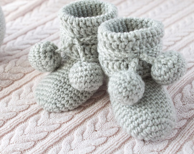 Crochet booties with large pom poms