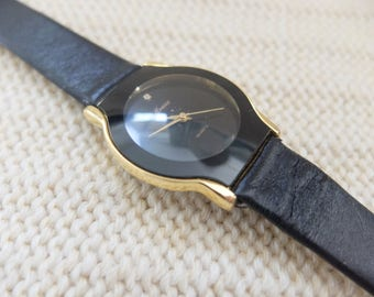 Minimal black / gold 1980s Moniex watch with rhinestone and black leather band