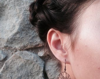 "Earring is ""Subtle"" crocheted with brown colored copper wire, slight tendency."