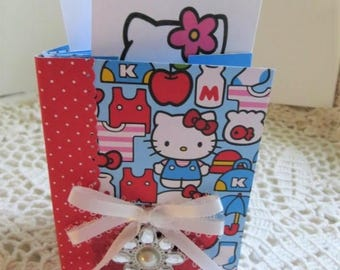 "Hello Kitty mini album (paper) w/ pockets, 3"" x 4 -1/2"" w/ matching gift bag, HK tags, gold bow, red, white, blue, pink, 8 pockets, 26 tags."