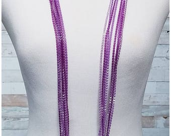 Long multi stranded plastic necklace in shades of purple and lavender