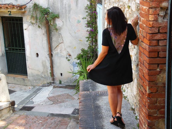 Black dress, short, trapeze, backless with inlay of embroidered tulle floral lace. Small short sleeves. Cocktail dress