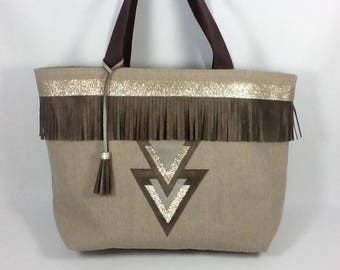 Tote bag in natural linen with gold graphic inserts and chocolate brown fringe