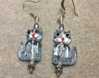 Translucent light blue lampwork cat bead earrings adorned with light blue Czech glass beads.