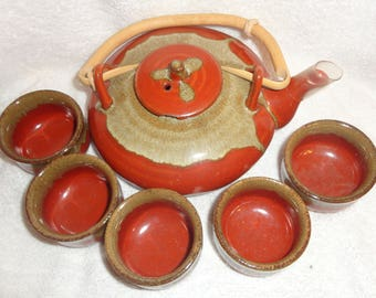 Beige and Redddish 6 pc oriental look tea pot and 5 cups.Estate sale find!!! Lovely pottery work, good quality and a bamboo handle.