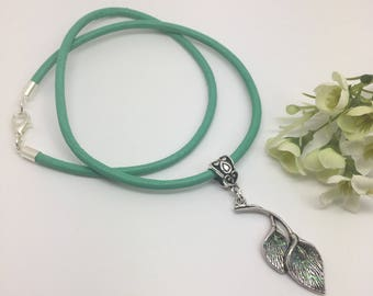 Sparkly Calla Lily necklace, on green leather.