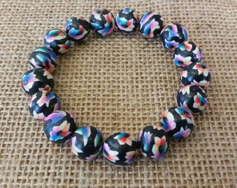 Chunky bead bracelet in a black and multicolour tropical flower pattern, colourful stretch bracelet