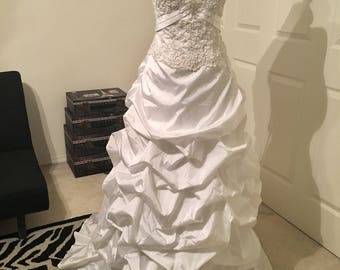 White strapless wedding gown. Bodice is covered in beaded appliqué and satin finish on bottom!