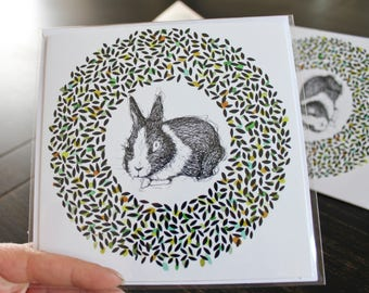 Greeting card with envelope white. Rabbit, circle, and reason. Black, white, green, turquoise and orange. 5.5 x 5.5 in..