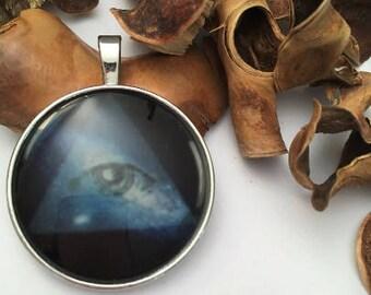 illustrated cabochon eye of horus Navy blue background, light blue eye triangle pendant