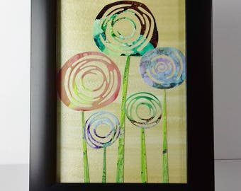 Abtract painting of flowers in black frame.
