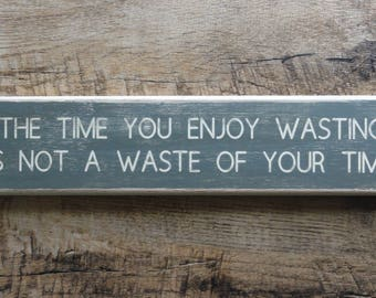 """Sign: """"The time you enjoy wasting"""" painted distressed wood sign."""