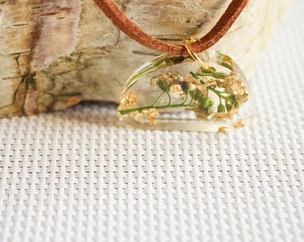 A resin pendant with real flowers and gold leaf