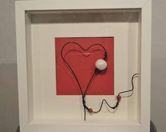 White frame representing a heart in annealed iron wire, on red and white Pearly ceramic bead