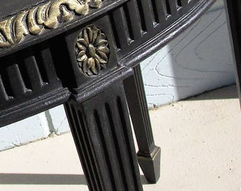 A black and gold painted side table on fluted legs.