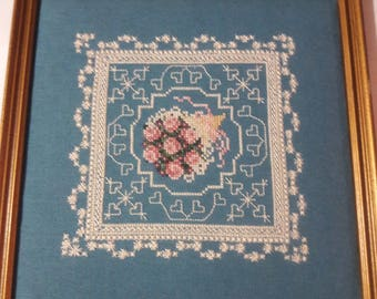 """Vintage 9x9"""" completed Crossstitch.Blue background, off white cross stitches and floral center"""