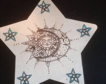Sun and moon design burned onto star shaped sign