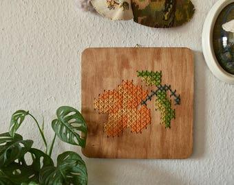 Handgemaakt geborduurd muurdecoratie - hout paneel met een oranje bloem. Een bloemetje voor je interieur