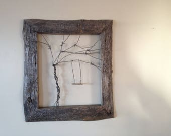 Reclaimed barn wood frame with Barbed wire tree.