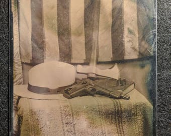 Still life Americana dryplate tintype of an m1911 pistol, tomahawk hat and Bible.