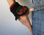 freeform crochet cuff bracelet with green and red beaded crochet flowers and black crochet lace