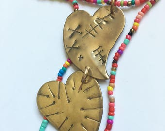 Healing pincushion hearts in brass with beaded necklace