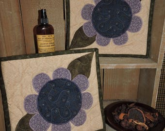 "Two Potholders with an Appliqued Plum and Navy Flower on a Tan Background     11"" x 10.25"" Each"