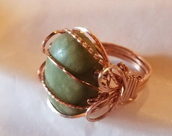 Style conscious rose gold wraps a smooth green cabochon 20x16mm in a classy Pharoah design with a twist creating a more feminine effect.