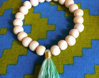 Beaded bracelet with tassel in gradient colors of green and light wood