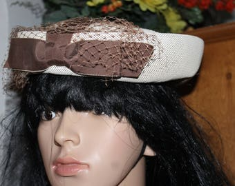 This hat is shaped with a top and a rim and a bow with mesh on the front, it is off white with a brown bow, Church, Easter, Funeral, NICE