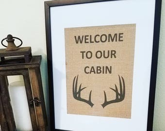 Welcome to our cabin,Burlap sign,Welcome sign,Antlers,Deer,Rustic home,Hunting,Family cabin,Christmas,Cabin decor,Lake house,What happens