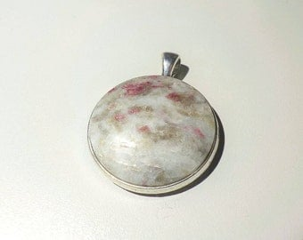 Pink Tourmaline in host rock natural stone pendant.  30 mm diameter stone.  Silver plated metal alloy. 19.6 grams in weight.