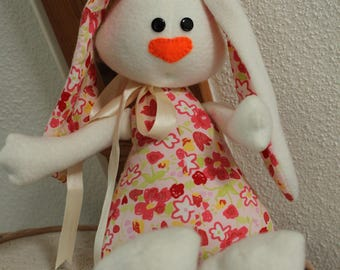 Plush white rabbit and pink flowers