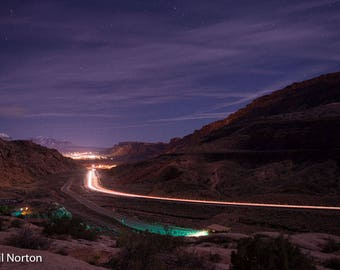 Desert Lights is a time exposure taken from Arches National Park viewed down the mountain to Moab and the Colorado River headwaters