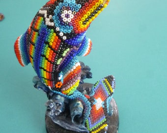 Hand beaded Huichol dolphin on a clay and wooden base.