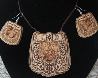 Set of birch bark pendant on leather cord and birch bark earrings .