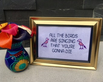 All the birds are singing that you're gonna die 4 x 6 inch Nihilist Needlepoint in gold frame