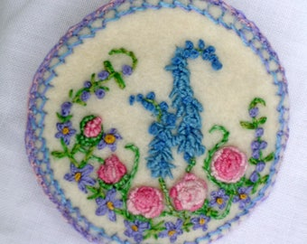 Roses and cottage garden flowers on a near-white felt brooch