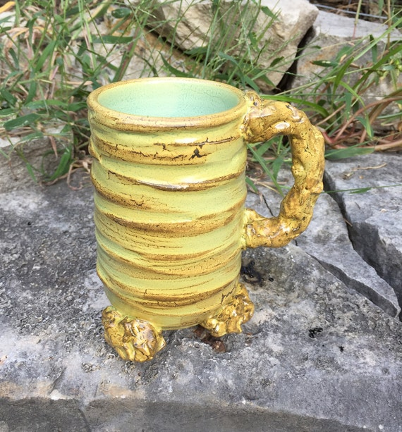 porcelain mug in beige, golden yellow, and pale green