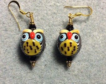 Black and yellow lampwork spotted owl bead earrings adorned with black Chinese crystal beads.