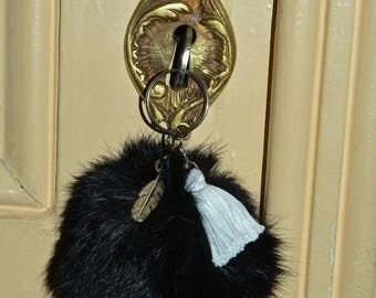Plush black pompom key ring and its charm