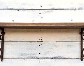 """Rustic wood wall shelf (natural wood with gray wash) with decorative cast iron corner brackets; 31"""" L x 7"""" W"""
