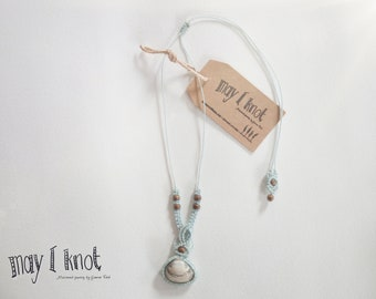 light blue macrame necklace with a shell